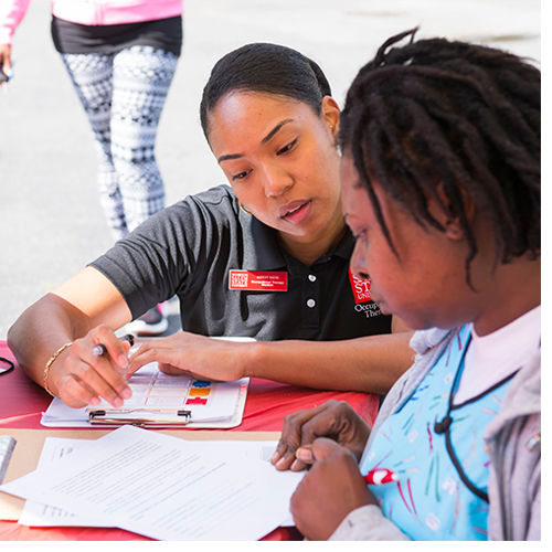 An occupational therapy student assists a patient at the Rams Know H.O.W. Mobile Unit. Occupational therapy is one of six WSSU graduate programs that will benefit from a $2.4 million federal grant. (May 2016 file photo)