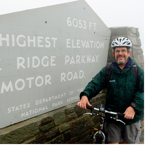 Brian Railsback takes a break at Richland Balsam, the highest point reached by the Blue Ridge Parkway, during his pledge ride for Honors College scholarships in 2013.