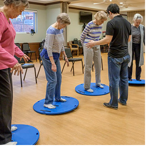 UNCG researchers observe Well•Spring residents on wobble boards.