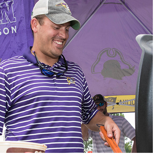 Zach Daugherty, who earned his accounting degree in 2012 and his MBA in 2015 from ECU, cooks shrimp wrapped in bacon with honey chipotle barbecue sauce -- his opening day tradition – during the Sept. 2 pre-game tailgate at ECU. (Photos by Rhett Butler)