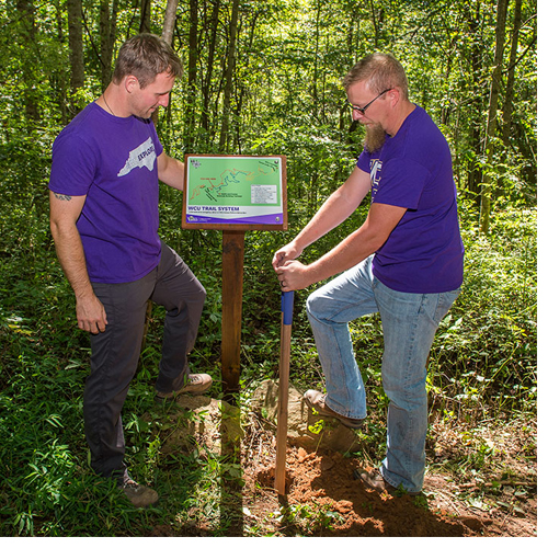 Jeremiah Haas (left), WCU's associate director for outdoor programs, and Josh Sanders, building and environmental services technician in the Department of Campus Recreation and Wellness, install a map at one of the major trail system intersections. (Photo by David McNally.)
