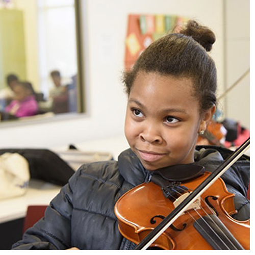 The Professional Development for Arts Educators grant is a natural extension of the College of Visual and Performing Arts' community-engaged work with local schools. In the photo above, a student learns violin as part of the Arts After School initiative.