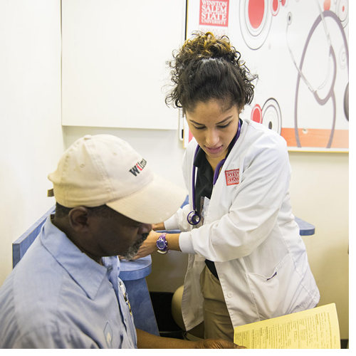 A WSSU School of Health Sciences student assists a patient at the Rams Know H.O.W. mobile unit.