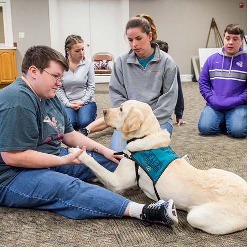 Emily Roberson, a young adult on the autism spectrum, works with a recreational therapy dog from PAWS 4 LIFE.