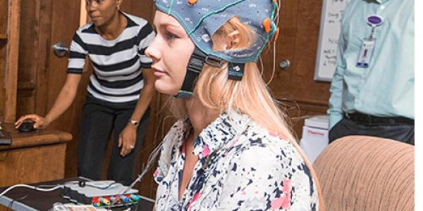 Psychiatrist Vivek Anand, right, and research coordinator Janet Benjamin, left, are conducting a study analyzing the brain's response to smoking imagery. Madison Neves is pictured wearing an EEG cap. (Photos by Cliff Hollis)