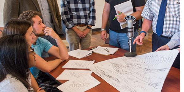 "Members of the cast and production team for ""A Sci-Fi Double Feature"" look over a set of blueprints for the Nautilus submarine from ""20,000 Leagues Under The Sea"" prior to a recent rehearsal."