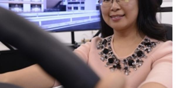 Psychologist Jing Feng sits behind the wheel of NC State's driving simulator on west campus.